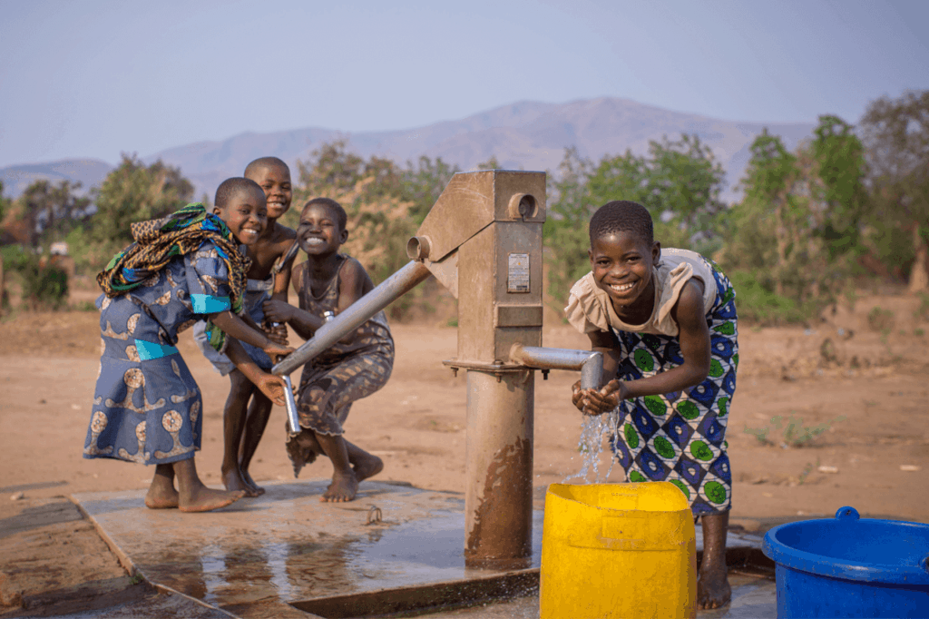 Children playing by hand pump