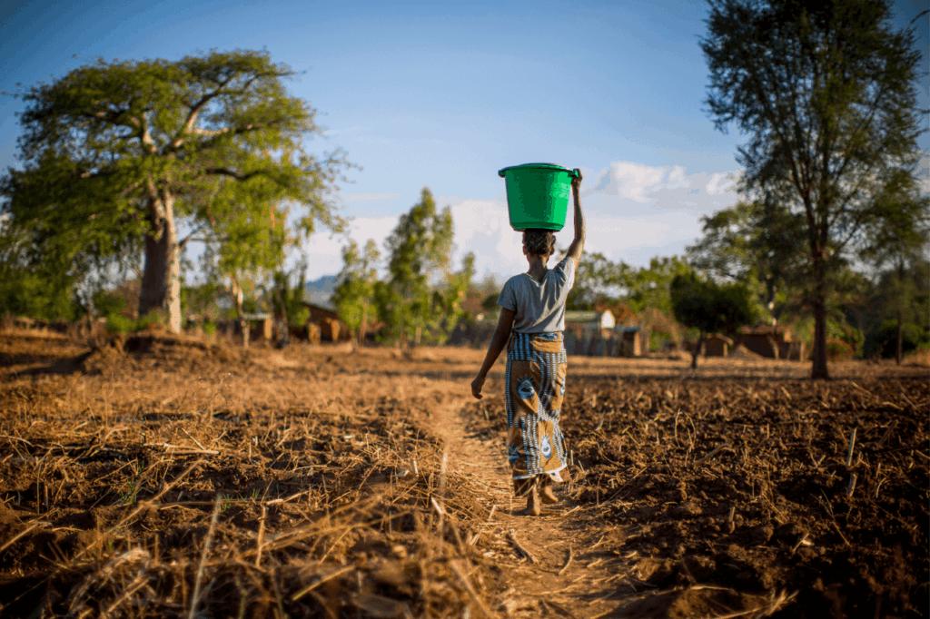 Lady walking through village with water