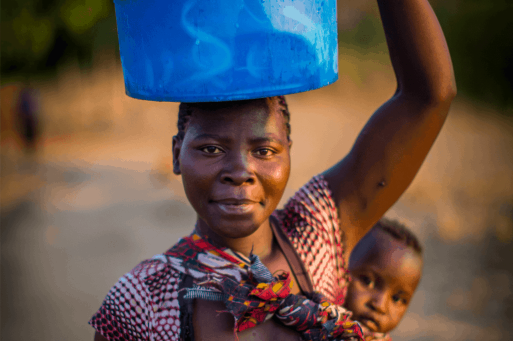 Woman carrying a baby on her back, and water