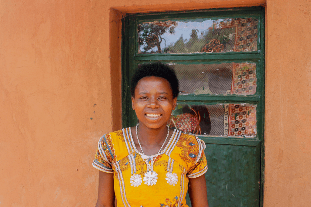 Woman smiling at the camera outside her house in Rwanda