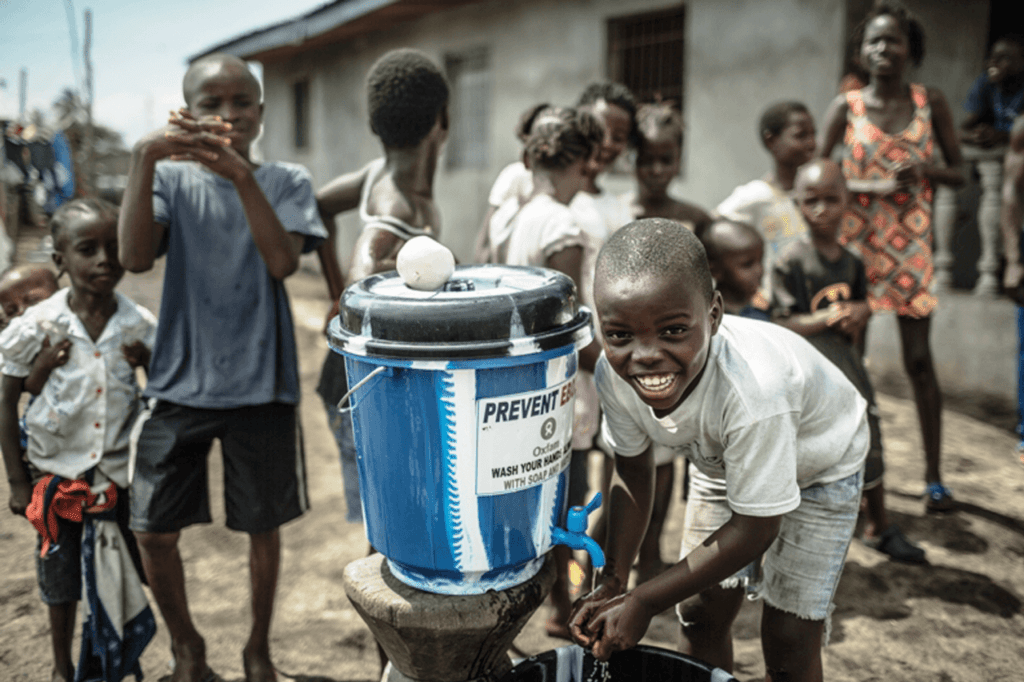Child washing his hands with a funded handwashing station to prevent Ebola