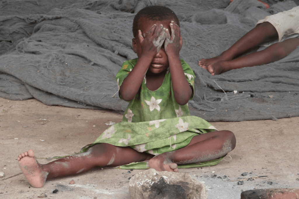 Child covered in dirt covering eyes
